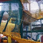Spiraling climbing net with mouse holes for people to pass through