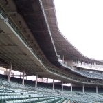Public safety netting suspended from stadium balcony seating protects the crowds below for falling or thrown debris.