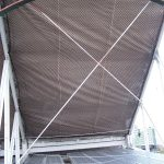 A netting panel mounted on the underside of a stadium bleacher.
