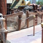 A themed waiting cue line, using mesh netting for a barrier railing.