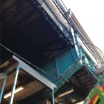 Safety netting installed on the underside of a commuter rail platform.