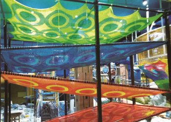 Multi-colored climb netting system of ramps in a children's play area.