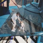 A father and his baby son stand on a net platform.