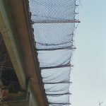 Safety netting installed on outrigger poles along an elevated highway.