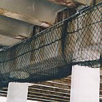 Debris netting wrapping a cement beam under an elevated highway.
