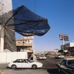 A 30 foot arm suspends a safety debris net over the street protecting cars and pedestrians.