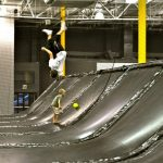 A child does a backflip in a trampoline park.
