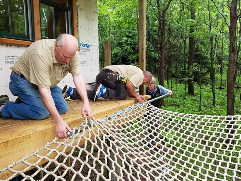 Attaching a climbing net deck to the tree house.