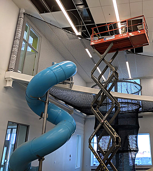 A climbing playscape being installed in a children's museum.