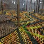 A colorful climbing net platform.