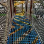 a colorful net bridge connecting elevated climbing structures