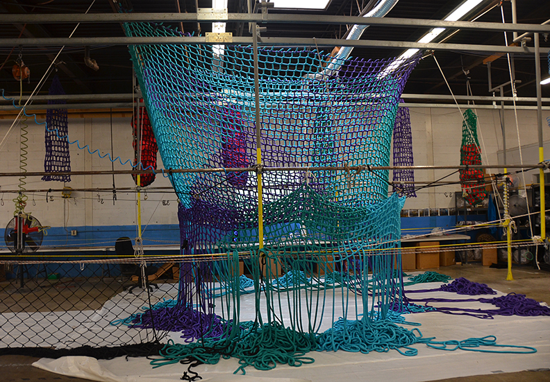 A Colorful climbing net being manufactured by hand.