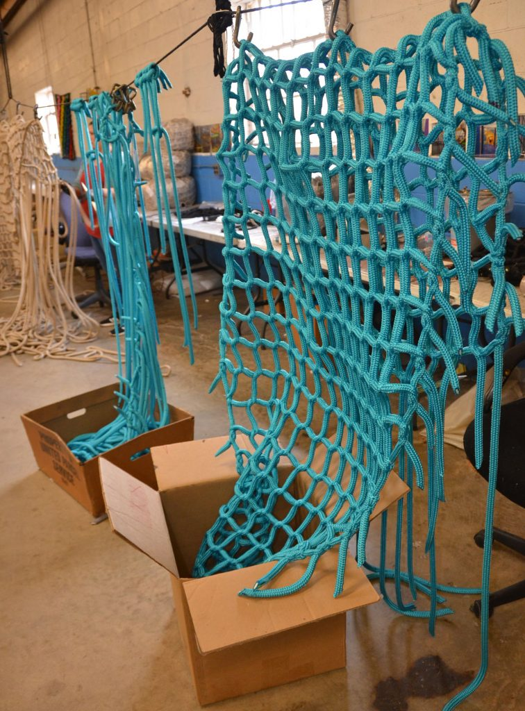 A teal climbing net is made by hand.