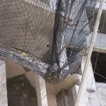 Debris safety netting on construction project catches heavy load of debris