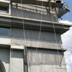 Facade netting conforms to the shape of architectural details on a building during reconstruction.