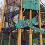 a climbing net leads up to a net bridge at The Monster Clubhouse at Sesame Place