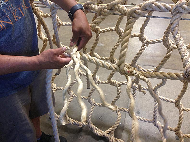 Hand making a rope climbing net.