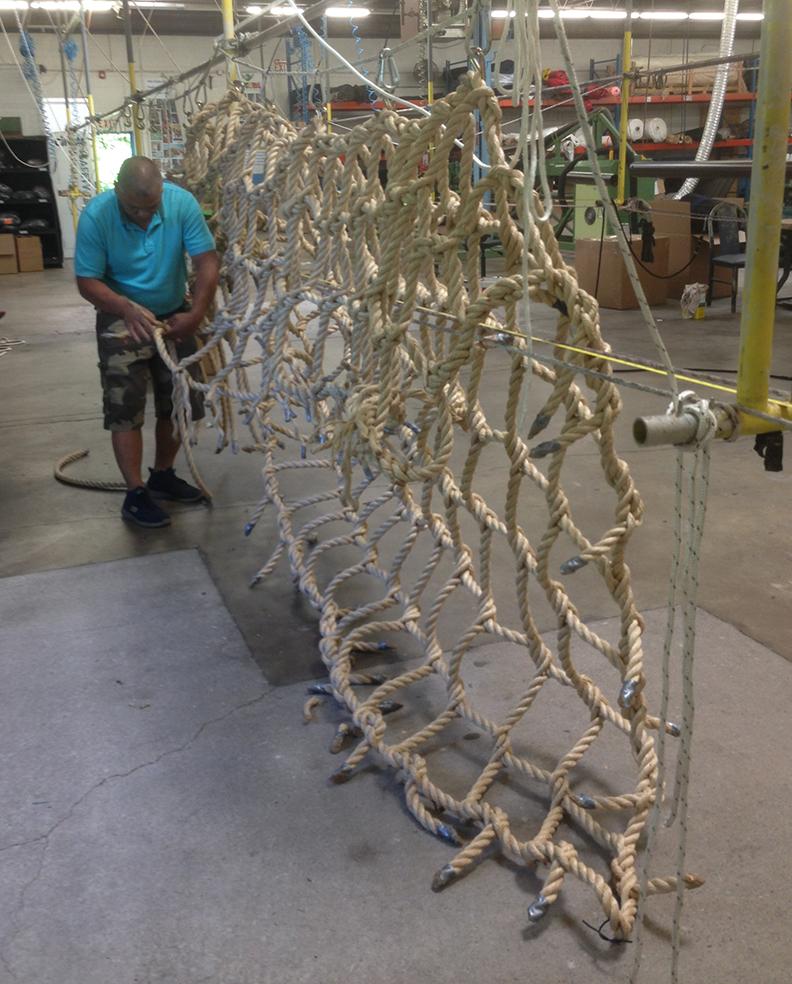 A hand woven rope climbing net being made.