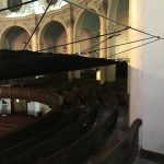 Debris netting suspended over the audience seating area in a church.