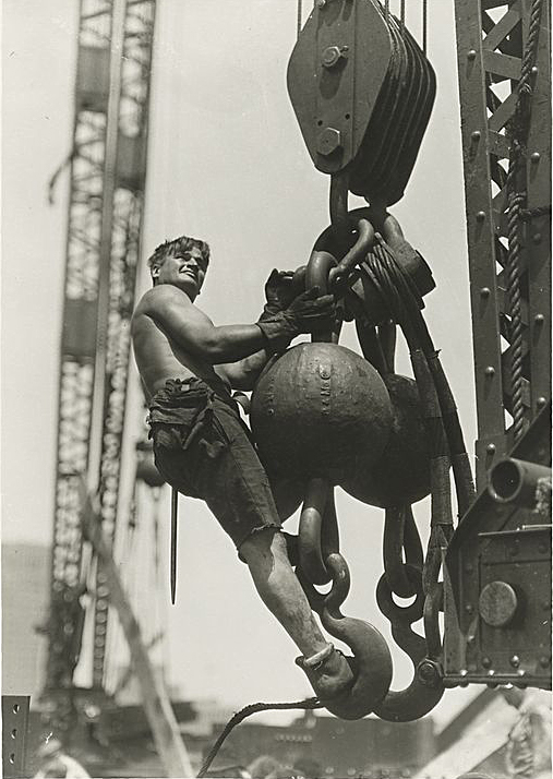 A construction worked rides a crane's lifting cable.