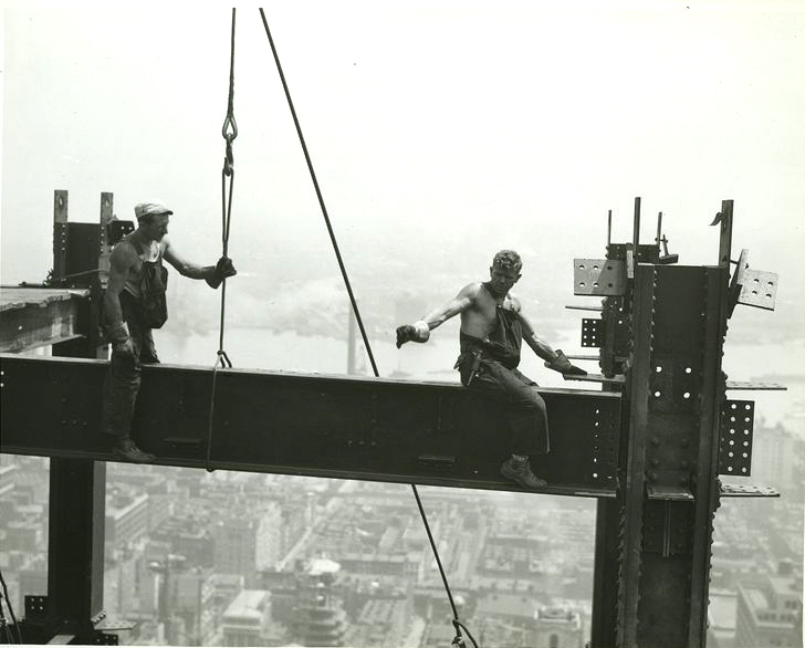 Two steel workers straddle a beam during the construction of The Empire State Building.