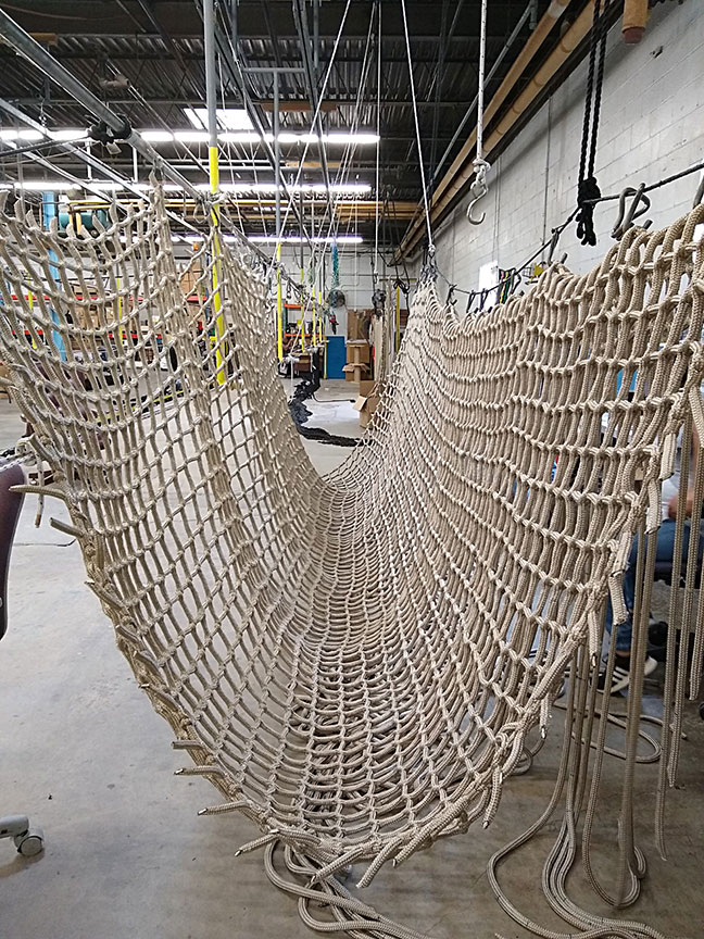 A rope net bridge being manufactured.