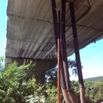 Netting supports a layer of tarps suspended under a bridge undergoing restoration.