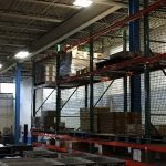 Storage rack safety netting installed in a warehouse.