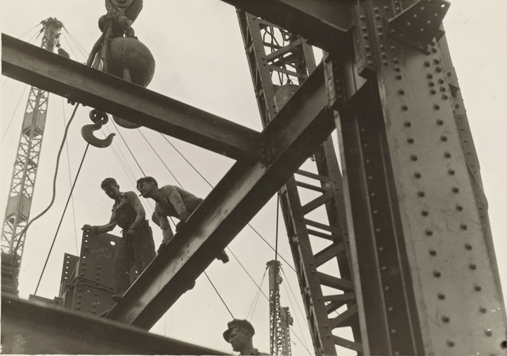 Two steel workers balance on a beam, waiting for a crane to raise cargo.