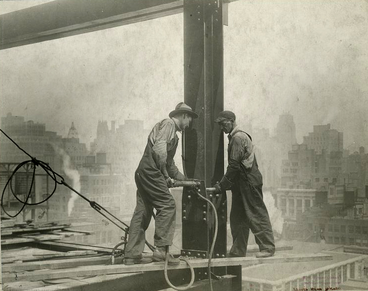 Steel workers applying rivets to a column.