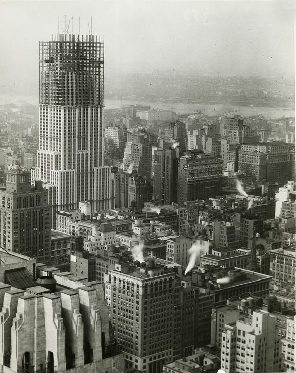 The Empire State Building during construction, raises far above the rest of the neighborhood.