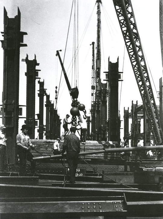 Steel workers wait to load steel beams on a crane.