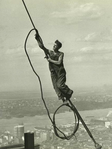 A steel worker climbs a cable.