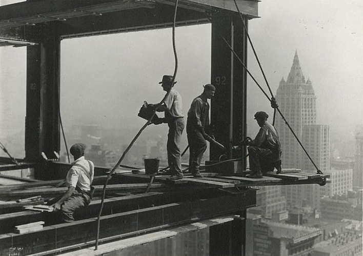 Workmen apply rivets to a beam of The Empire State Building.