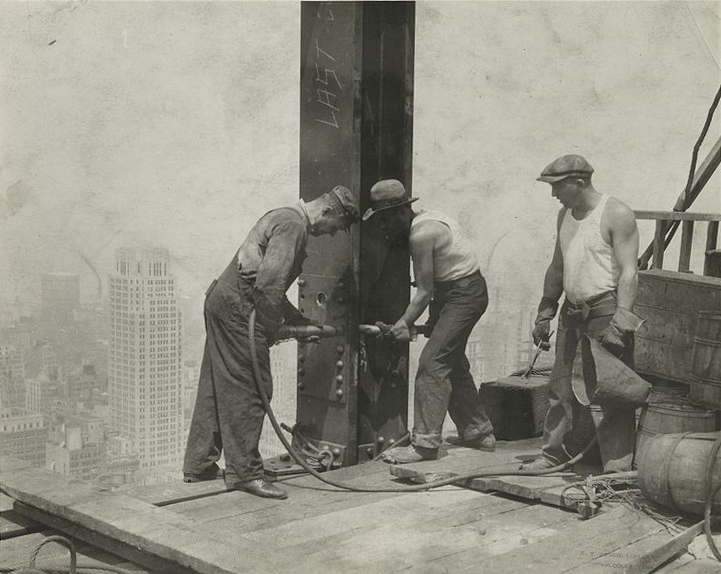 Steel workers putting rivets into a steel column on the Empire State Building.
