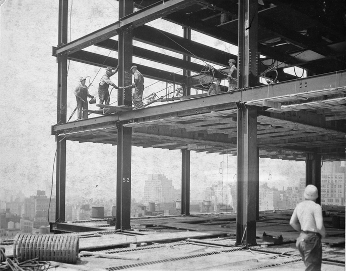 Steel workers walk the beams of the Empire State Building during its construction.