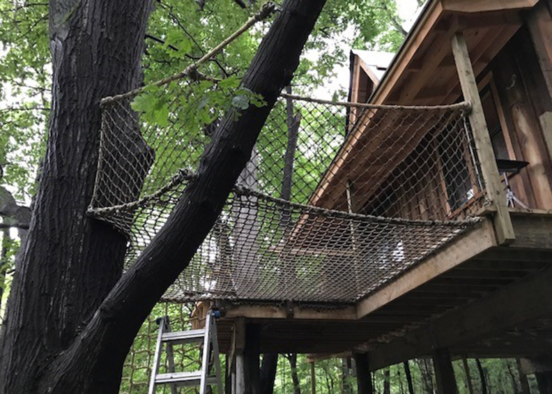 A netted platform attached to a tree house.