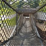 A netted tunnel bridge in a playground.