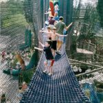 Families playing on a rope bridge.