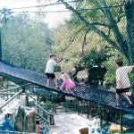 A rope and net bridge with children and their parents.