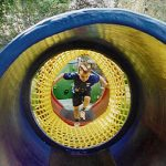 Little children playing in a netted tunnel.