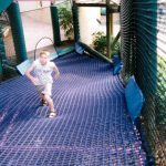 A boy on a climbing net ramp.