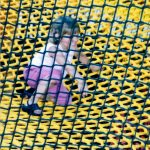 A Little girl sitting on a yellow climbing net.