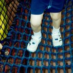 A child's feet walking on a net bridge.