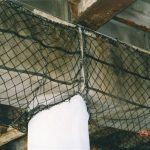 Containment netting installed under a bridge to secure spalling concrete.