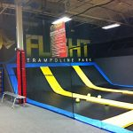 Barrier netting at a trampoline park keeps activities separate.