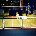 A children's museum uses mesh netting as a border rail for a racetrack exhibit.