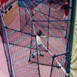 A boy wandering through a maze made of netting.