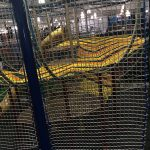 A netted climbing structure as seen through barrier netting.