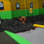 A child leaps into a foam cube pit at a tramploine park.